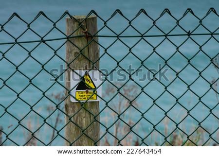 Cliff hazard sign on wooden post - stock photo