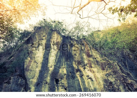 Cliff in forest ( Filtered image processed vintage effect. ) - stock photo