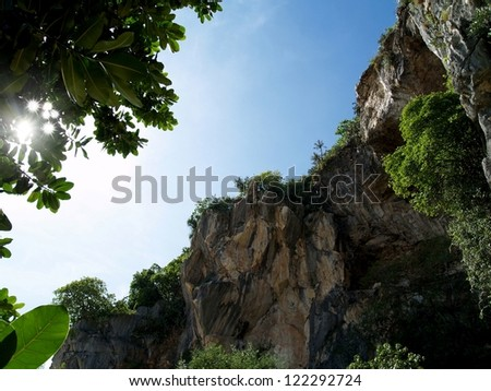 Cliff, sky, trees, leaves and sun - stock photo