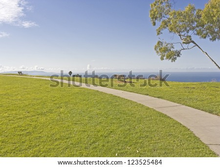 Cliff top scenic view. Wide angle perspective of a curving paved path in a suburban park. Wood benches sit on the grassy cliff top overlooking the blue sky, clouds, and ocean. - stock photo
