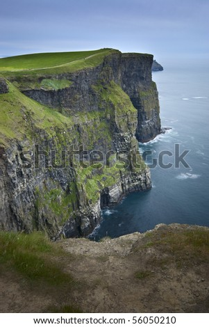 Cliffs of Moher at twilight. Vertical orientation view with pathway at bottom of frame. - stock photo