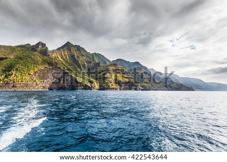 Cliffs of the Na Pali coast in late afternoon sun with darkening skies above. Kauai, Hawaii - stock photo