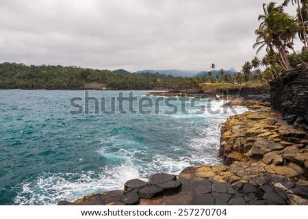Cliffs on a tropical shore with palm trees and pristine blue sea. Boca do Inferno, Sao tome and Principe. - stock photo