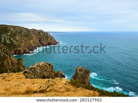 "Cliffs seen from ""Cabo da roca"" cape in Portugal, Sintra municipality. It's a  western most extent of mainland Portugal and continental Europe.Cloudy day, cliffs, waves crashing, dark blue sea."