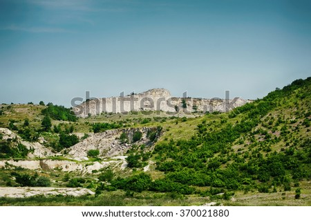 Cliffs With Green Trees Over Blue Sky - stock photo