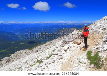 Climber admires the beautiful views towards Alto Adige, Catinaccio massif, Dolomite Alps, Italy