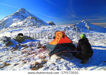 Climber arranges the tent site in winter - stock photo