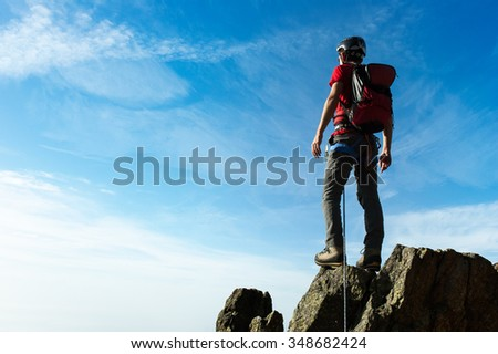 Climber arrive on the summit of a mountain peak. Concepts: victory, success, achievement, triumph. - stock photo
