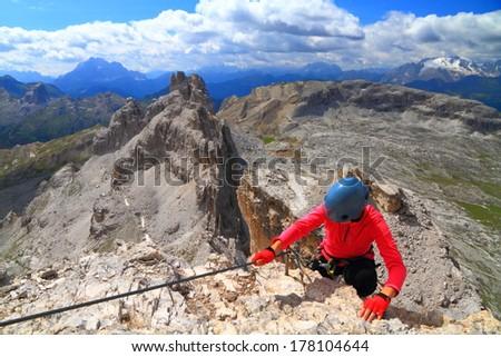 Climber arrives on the mountain summit, Dolomite Alps, Italy - stock photo