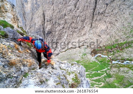 "Climber ascending exposed wall above distant ground on via ferrata ""Brigata Tridentina"", Sella massif, Dolomite Alps, Italy - stock photo"