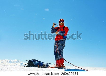 climber at the top of a pass with backpacks meeting the sunrise in the mountains and photographs on the phone - stock photo