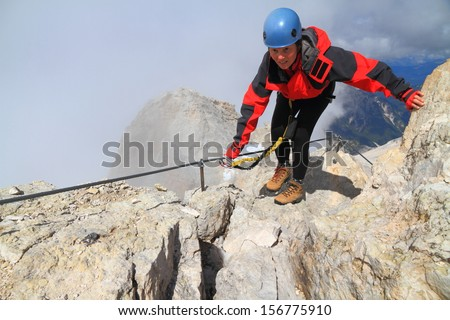 Climber balancing on Monte Cristallo's via ferrata Marino Bianchi, Dolomite Alps, Italy - stock photo