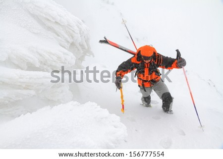 Climber carrying skies on the backpack in bad weather - stock photo