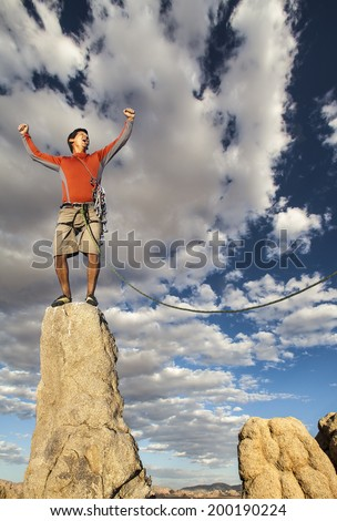 Climber celebrates on the summit of a challenging cliff. - stock photo