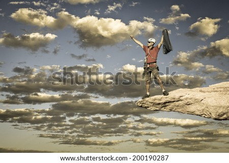 Climber celebrates on the summit of a challenging cliff.