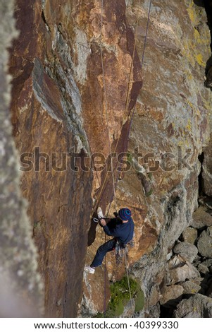 Climber climbing up the cliffs at Rhoscolyn Anglesey North Wales