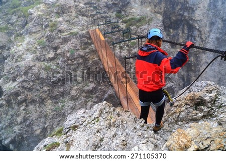 "Climber crossing a wooden bridge across deep gap along via ferrata ""Brigata Tridentina"", Sella massif, Dolomite Alps, Italy - stock photo"