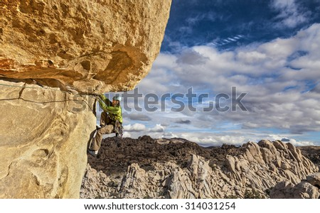 Climber dangles from the side of a cliff. - stock photo