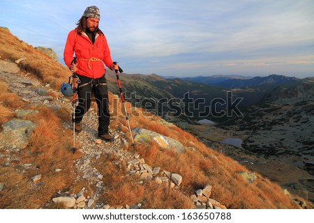 Climber descending a mountain slope in the sunset light - stock photo