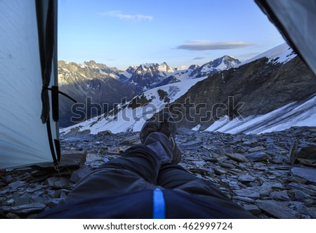 Climber enjoying the evening view from his tent high up in the Swiss mountains.