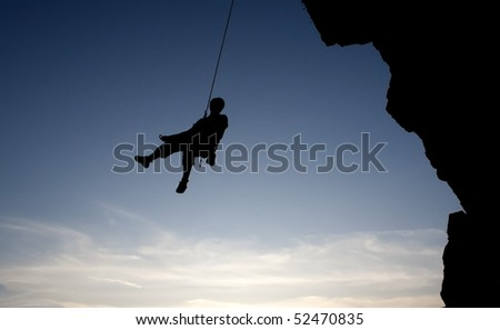 climber hanging on rope - stock photo