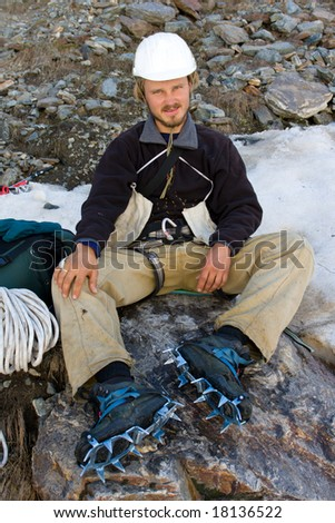 Climber in helmet and crampon sitting on stone