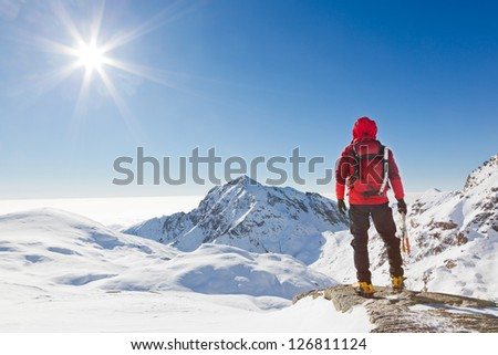 Climber looking at a snowy mountain landscape in a sunny winter day.. Western Alps, Biella, Italy. - stock photo