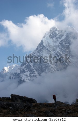 Climber looking at mountain covered with snow, Himalaya - stock photo
