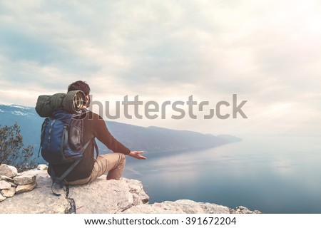 climber meditating on the top of the mountain with a lake view