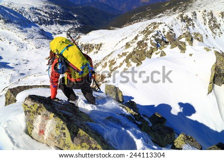Climber on difficult trail on top of the snow covered mountain