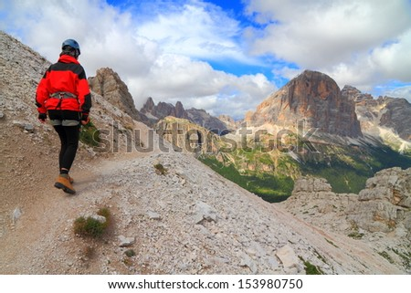 Climber on mountain trail towards via ferrata route, Dolomite Alps, Italy