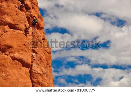 Climber on red rock against blue sky and white clouds