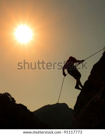 Climber on sunset sky background - stock photo