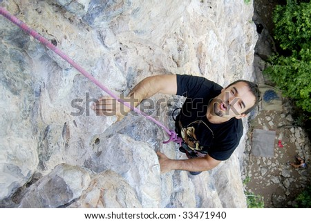 Climber overpassing a difficult part in the wall while rock climbing in Phi Phi Islands, Thailand - stock photo