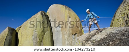 Climber rappelling from the summit of a rock spire after a challenging ascent. - stock photo