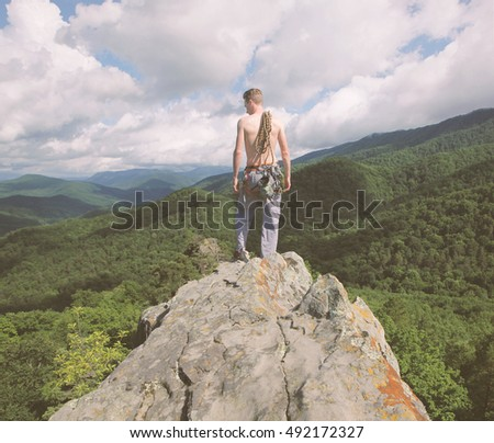 Climber standing on top of rock.