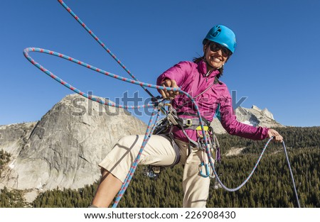 Climber struggles for her next grip on the edge of a challenging cliff.
