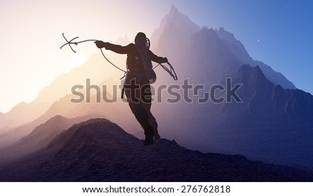 Climber throwing the hook in the mountains. - stock photo