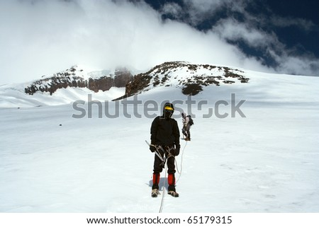 climber walking up by the snowfield to the high summit - stock photo
