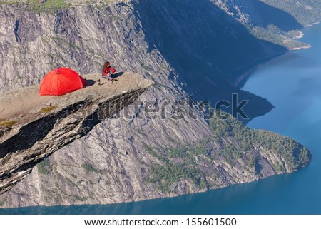 climber with a tent on the rock top - stock photo