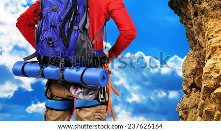 climber with backpack looking to yellow mountain - stock photo