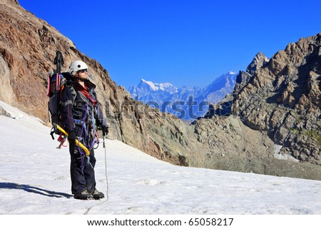 Climber with climbing equipment on the snowy mountain - stock photo