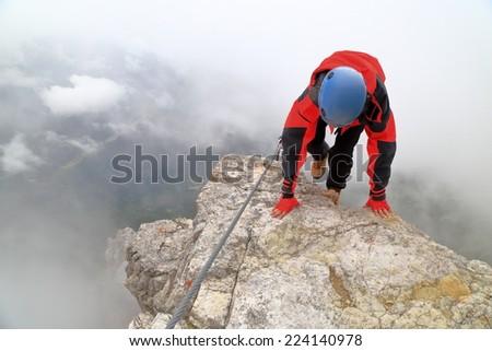 """Climber woman arrives on a small ledge on via ferrata """"Punta Ana"""", Tofana massif, Dolomite Alps, Italy - stock photo"""