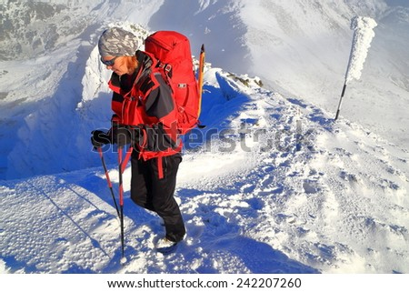 Climber woman ascending a snowy mountain in winter