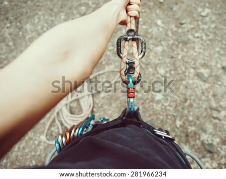Climber woman in harness with rope and equipment eight. Point of view shot - stock photo