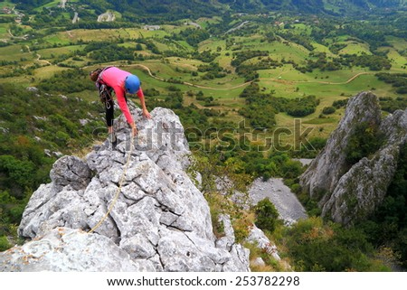 Climber woman on top of limestone ridge in fine summer day - stock photo