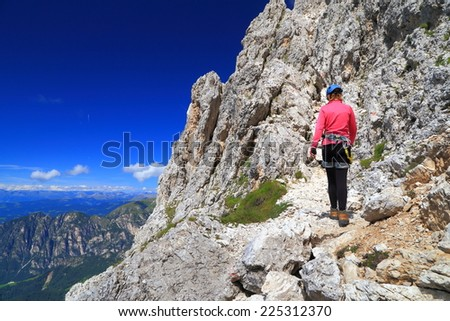 "Climber woman on via ferrata ""Passo Santner"", Catinaccio massif, Dolomite Alps, Italy"