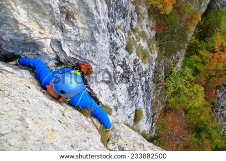 Climber woman stretching to a handhold on limestone wall  - stock photo
