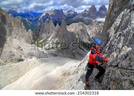 "Climber woman traversing along vertical wall, via ferrata ""Merlone"", Cadini di Misurina, Dolomite Alps, Italy - stock photo"