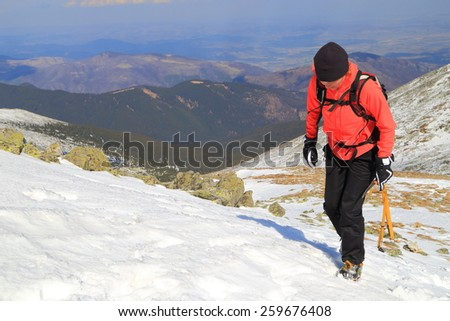 Climber woman using crampons and ice axe to ascend a snow covered mountain slope - stock photo